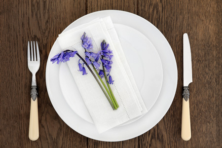 antique table: Dinner table place setting with white porcelain dishes, bluebell flowers, antique cutlery and  linen napkin over old oak background.