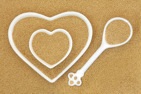 super food: Amaranth super food in heart shaped bowls and porcelain spoon forming an abstract background.