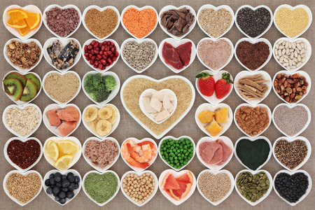 whey: Large health and body building high protein super food in heart shaped bowls with meat, fish, supplement powders, seeds, cereals, grains, fruit and vegetables.