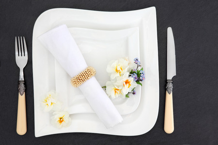 napkin ring: Table place setting with white porcelain dishes, spring flowers and antique cutlery with linen napkin and ring over slate background.