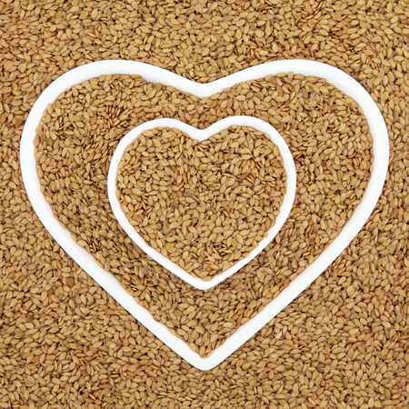 flaxseed: Golden flax seed health food in heart shaped porcelain bowls forming an abstract background. Stock Photo