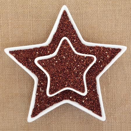 super food: Quinoa grain super food in star shaped dishes over hessian background. Salvia hispanica. Stock Photo