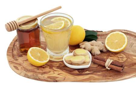 superfood: Cold and flu remedy cure drink in a glass with fresh ginger, lemon, honey in a jar with dropper and cinnamon spice on an olive wood board over white background.