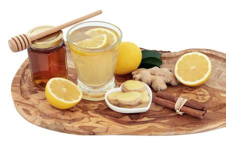 gripe: Fr�o y el remedio contra la gripe bebida cura en un vaso con jengibre fresco, lim�n, miel en un frasco con gotero y canela especias en un tablero de madera de olivo sobre fondo blanco.
