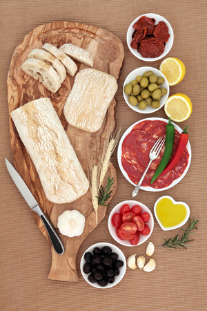 ridged: Italian antipasti selection with olives, salami, chilli peppers, sundried and fresh tomatoes, garlic, lemon, oil, with ciabatta bread on an olive wood board on brown ridged paper  background.