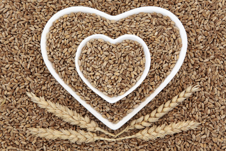 dietary fiber: Wheat grain food in heart shaped bowls with sheaths forming an abstract background.