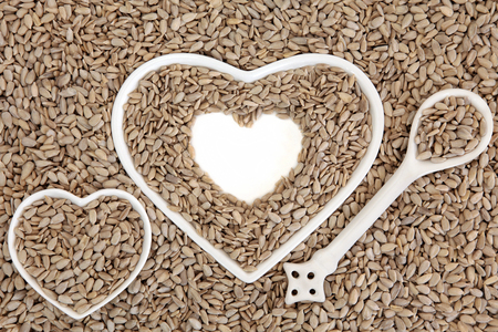 abstract seed: Sunflower seed health food in heart shaped porcelain bowls and spoon forming an abstract background. Stock Photo