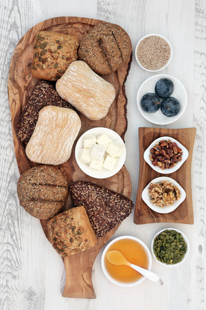 greek food: Healthy greek food with feta cheese, figs, nuts and seeds, honey and bread roll selection on olive wood board over distressed wooden background.