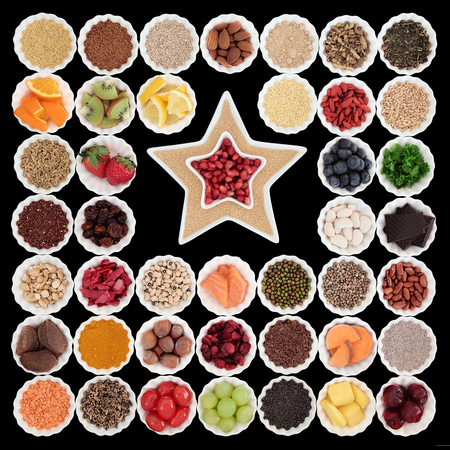 maca root: Large health and superfood collection in porcelain bowls with star shaped dishes over black background. High in vitamins and antioxidants. Stock Photo