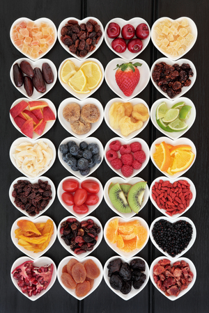 super fruit: Large mixed fruit background super food selection with fruits high in antioxidants, vitamin c and dietary fibre in heart shape dishes.