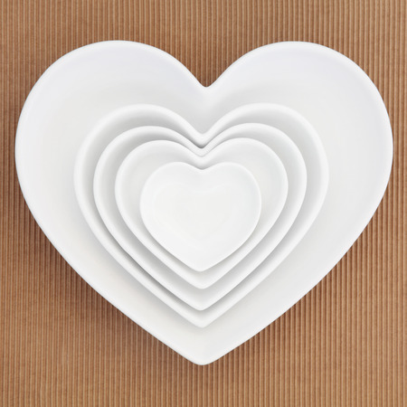 ridged: Heart shaped porcelain dishes of varying sizes over ridged brown paper background.