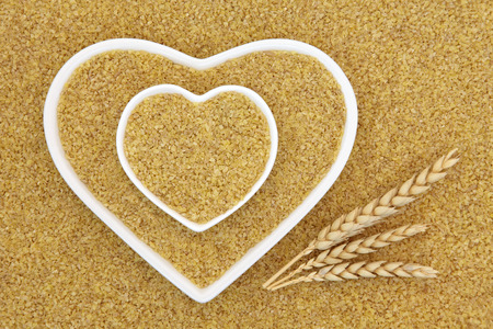 super food: Bulgur wheat super food in heart shaped bowls with wheat sheaths forming an abstract background. Stock Photo