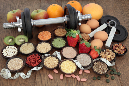 hand gripper: Body building dumbbells and hand grippers with health and super food selection including supplement powders  and fresh fruit with tape measure over oak background.