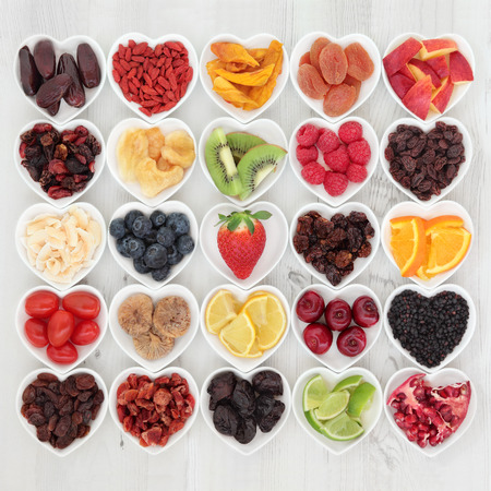 selection: Healthy superfood fruit selection in heart shaped porcelain dishes over distressed wooden background, high in vitamins and antioxidants.