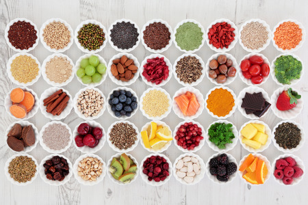 Large super food selection in porcelain crinkle bowls over distressed wooden background. High in vitamins and antioxidants.