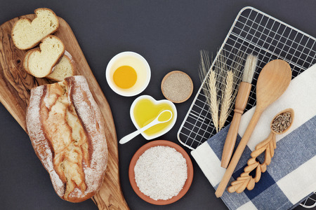 french bread: French bread loaf with baking ingredients and utensils with wheat sheaths and grain in a lovespoon on grey  background.