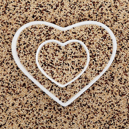 tricolour: Tricolour quinoa grain super food in heart shaped bowls forming an abstract background. Salvia hispanica. Stock Photo