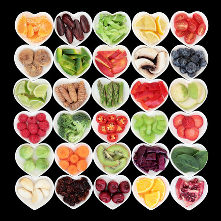 super fruit: Large health and super food fruit and vegetable selection in heart shaped dishes over black background. Stock Photo