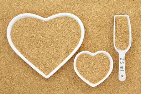 riboflavin: Amaranth super food in heart shaped bowls and porcelain scoop forming an abstract background. Stock Photo
