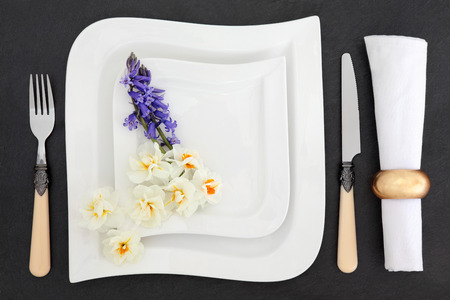 antique dishes: Elegant place setting with white porcelain dishes, antique cutlery, spring bluebell and narcissus flowers with napkin and ring over slate background.