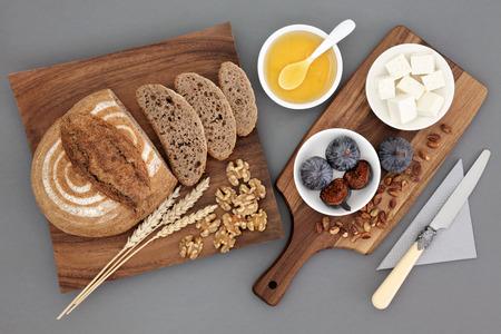 queso: Griega bocadillos con queso feta de queso, miel, higos, nueces y pistachos con pan de centeno y trigo vainas sobre tablero de madera de arce sobre fondo gris. Foto de archivo