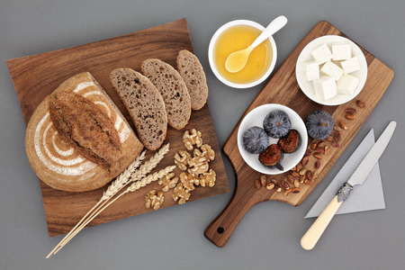 Griekse hapje eten met feta kaas, honing, vijgen, walnoten en pistachenoten met roggebrood en tarwe scheden op esdoorn houten bord over grijze achtergrond.