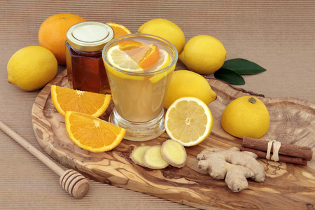 cold beverages: Vitamin c health remedy relief drink for cold and flu, with lemon and orange fruit, ginger and cinnamon spice and honey on an olive wood board.