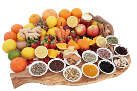 cold cure: Large food and medicinal herb selection for cold remedy with foods high in antioxidants on an olive wood board over white background.