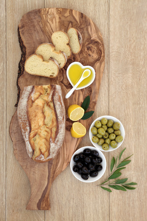 al fresco: Olives with fresh homemade bread on an olive wood board with leaf sprigs, lemon and oil over oak background. Stock Photo