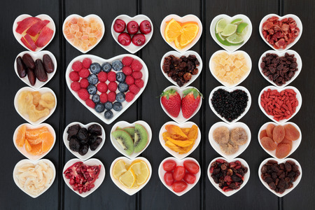 cherry: Fresh and dried mixed fruit superfood selection in heart shaped bowls over wooden black background.