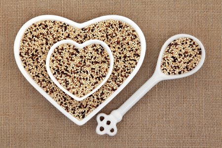 tricolour: Tricolour quinoa grain super food in heart shaped bowls and porcelain spoon over hessian background. Stock Photo