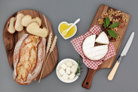 feta cheese: Healthy cheese snack with feta and camembert, olive oil, herbs, walnut and pistachio nuts, with fresh bread loaf and wheat sheaths on maple boards.
