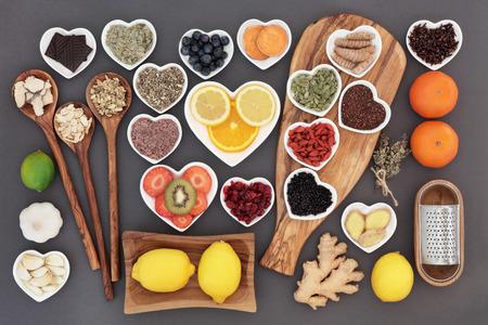 gripa: Selección de la comida y la hierba para el Super remedio para el resfriado y la gripe que incluye alimentos ricos en antioxidantes y vitamina c sobre fondo gris.