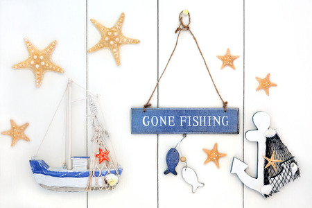 gone: Abstract background with gone fishing sign, starfish, decorative anchor and boat over white wood.
