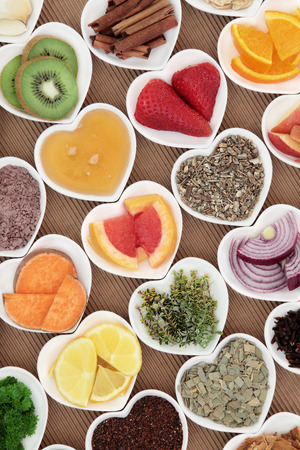 cures: Health food for flu and cold remedy cures high in antioxidants and vitamin c with medicinal herbs and spices in heart shaped dishes. Stock Photo