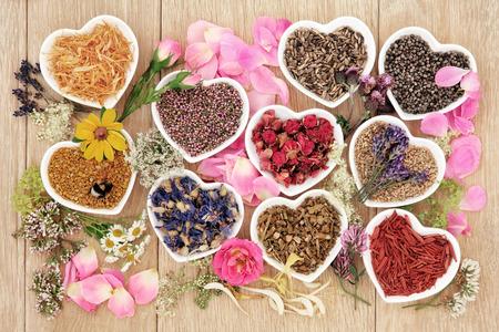 Curación de hierbas y la selección de flores utilizadas en la medicina natural en forma de corazón cuencos con polen y miel de abeja sobre fondo de roble. Foto de archivo