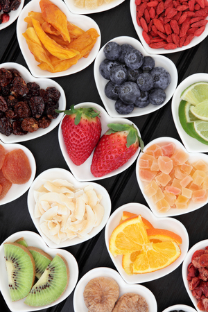 superfood: Healthy superfood fruit selection in heart shaped porcelain dishes over wooden black background, high in vitamins and antioxidants. Stock Photo