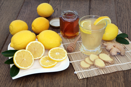cold cure: Natural cold and flu remedy drink in glass with fresh ginger, lemon and honey over oak background.