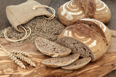 hessian bag: Fresh baked homemade rye bread on an olive wood board with wheat sheaths and grain in a hessian bag over  oak background.