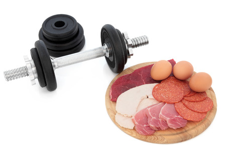 lean over: Body building high protein food of chicken, lean steak, bacon, salami and eggs with dumbbell weights over white background.