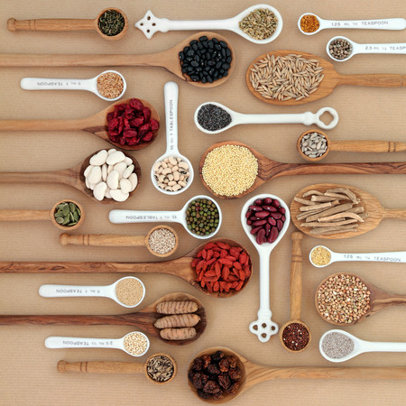dietary fiber: Dried superfood selection in spoons and bowls over natural paper background. Highly nutritious in antioxidants, minerals, vitamins and dietary fiber. Stock Photo
