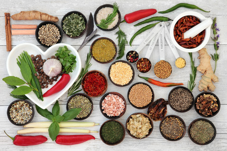 chili: Large fresh and dried herb and spice sampler with wooden bowls and china heart shaped dish with mortar and pestle over distressed white wooden background.