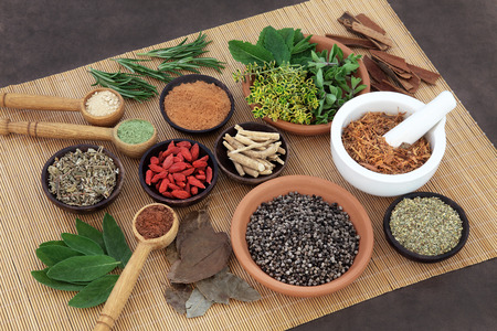 damiana: Herb and spice selection used in herbal health for men on bamboo mat.