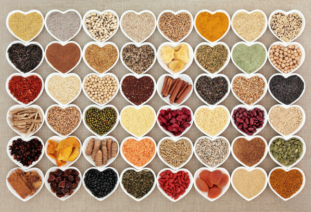 aphrodisiac: Dried super health food in heart shaped bowls over hessian background. High in minerals, vitamins and antioxidants.
