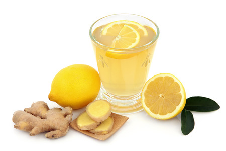 cold remedy: Cold and flu remedy drink in glass with fresh ginger, lemon and honey over white background. Stock Photo