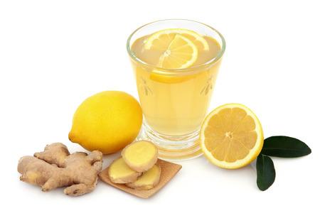 jengibre: Frío y gripe bebida remedio en vidrio con jengibre fresco, limón y miel sobre fondo blanco.