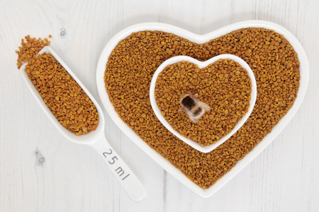 super food: Honey bee pollen grain super food supplement in scoop and heart shaped dishes over distressed wooden background. Stock Photo