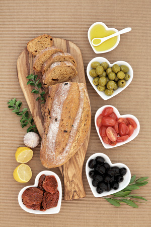 sun dried: Mediterranean antipasti with tomato and olive bread, olives, fresh and sun dried tomatoes, oregano herb with oil, garlic and lemon.