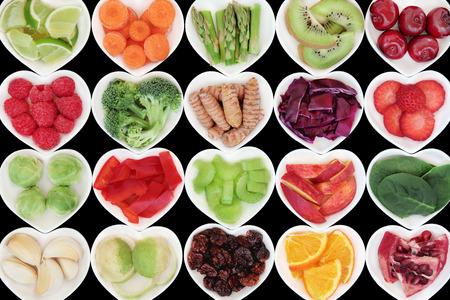 frutos secos: s�per alimento vegetal y la selecci�n de la fruta en forma de coraz�n platos de porcelana sobre fondo negro, con alto contenido de vitaminas y antioxidantes.