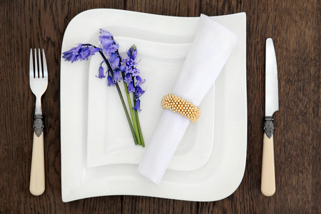 antique dishes: Table place setting with white porcelain dishes, bluebell flowers, antique cutlery and serviette with gold ring over old oak background.